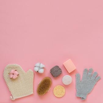 Accessori per la pulizia e il peeling della pelle sullo sfondo rosa.