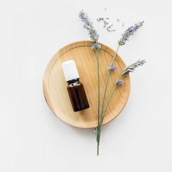 Olio per la pelle e fiori vista dall'alto minimalista