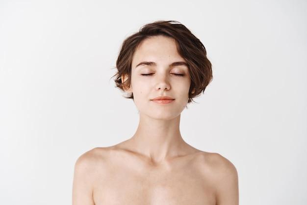 Cura della pelle e bellezza. primo piano di giovane donna senza trucco e spalle nude, chiudere gli occhi e sorridere teneramente, godendo di una sensazione fresca e pulita dopo la doccia, muro bianco