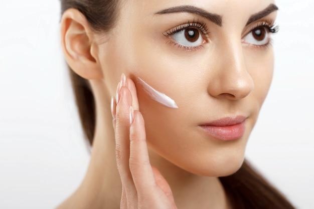Skincare beauty concept giovane donna graziosa che applica crema cosmetica