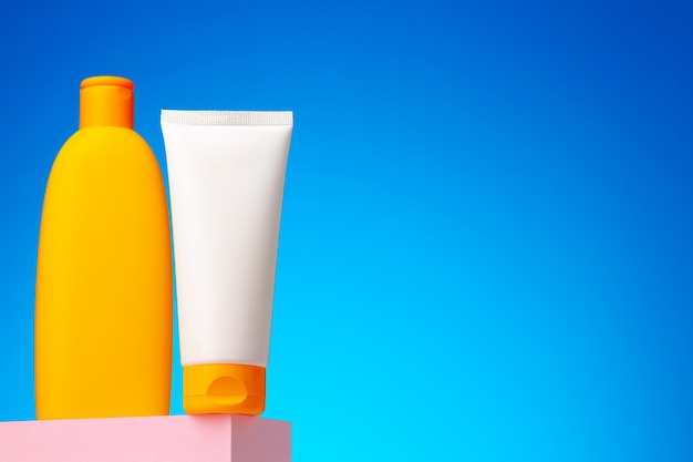 Contenitore di prodotti di bellezza per la cura della pelle su sfondo blu, copia dello spazio