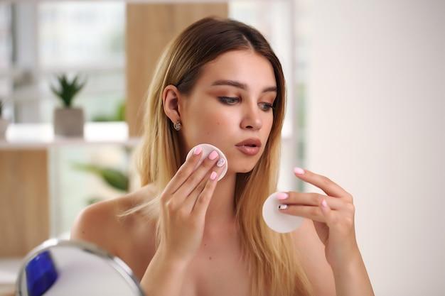 Concetto di cura della pelle, ritratto di donna felice che applica crema cosmetica sul viso