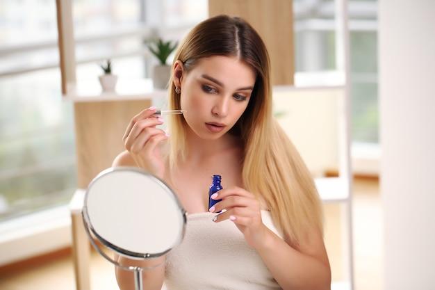 Concetto di cura della pelle, ritratto di donna felice che applica olio cosmetico sul viso