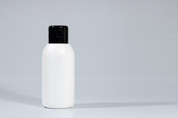 Flacone cosmetico per la cura della pelle su sfondo grigio bianco. cosmetici quotidiani. mockup di pubblicità di cosmetici