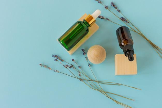 Olio per la cura della pelle, siero di lavanda, olio essenziale di lavanda. impostare prodotti cosmetici da bagno alla lavanda in bottiglie con fiori di lavanda secchi. prodotti termali naturali. trattamento aromaterapico per capelli.