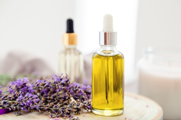 Olio per la cura della pelle, siero di lavanda, olio essenziale di lavanda. impostare prodotti cosmetici da bagno alla lavanda in bottiglie con fiori di lavanda freschi. prodotti termali naturali. trattamento aromaterapico per capelli.