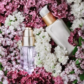 Prodotti per la cura della pelle - crema e siero - set con lillà fresco, colpo del primo piano, lilla come sfondo. cura della pelle e concetto di bellezza.