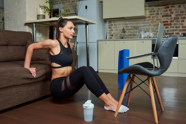 Una ragazza magra con un vestito attillato nero sta facendo esercizi per tricipiti e petto e guarda un video di formazione online su un laptop. un allenatore femminile che conduce una lezione di fitness a distanza a casa.