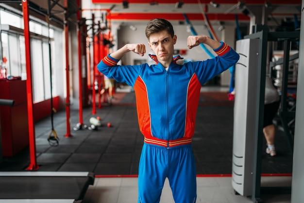 L'uomo magro in abbigliamento sportivo mostra i suoi muscoli in palestra, umorismo. persona di sesso maschile debole in un club sportivo