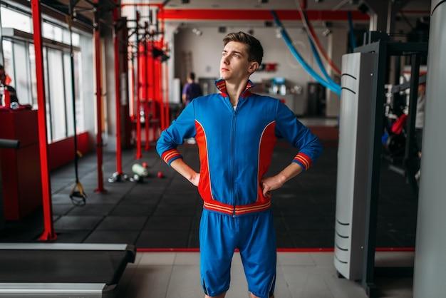 L'uomo magro in abbigliamento sportivo mostra i suoi muscoli, palestra