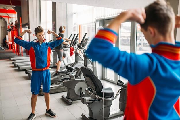 Uomo magro in abbigliamento sportivo guarda i suoi muscoli nello specchio in palestra, umorismo. persona di sesso maschile debole in un club sportivo