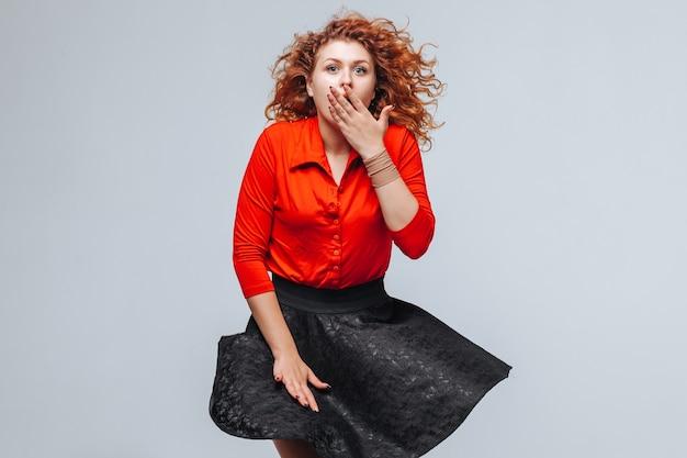 La gonna svolazza dal vento della ragazza dai capelli rossi su uno sfondo grigio chiaro
