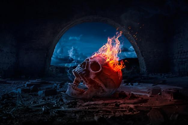 Teschio bruciato nel fuoco nella notte oscura di halloween. concetto di halloween