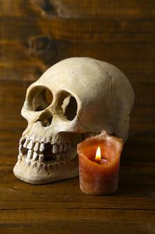 Teschio e candela su tavola di legno