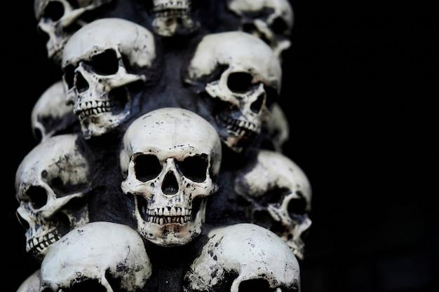 Sfondo di halloween del cranio molti teschi di persone stanno uno sopra l'altro. mistico concetto raccapricciante. memoriale occulto da incubo astratto
