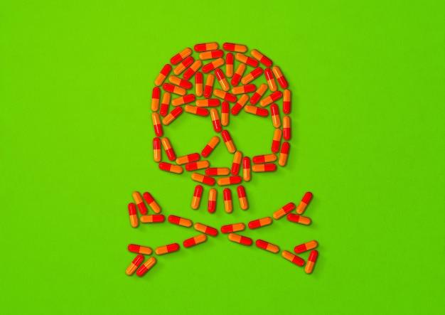 Cranio fatto di pillole capsula arancione isolato su sfondo verde. illustrazione 3d