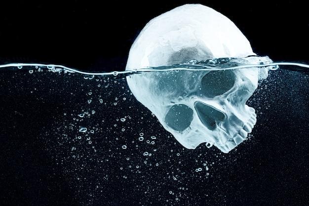 Modello di cranio che si tuffa in acqua su sfondo nero