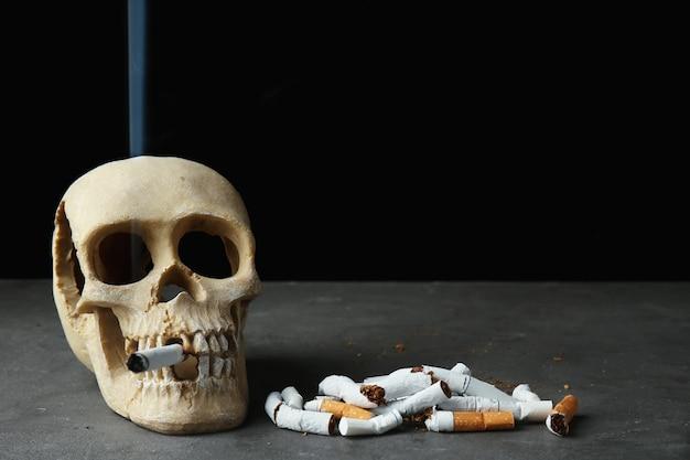 Teschio e mucchio di sigarette su sfondo nero