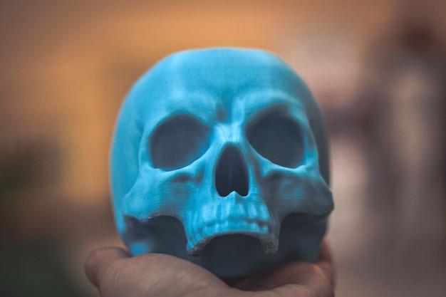 Teschio stampato su stampante 3d nella mano dell'uomo. tecnologia additiva moderna e progressiva