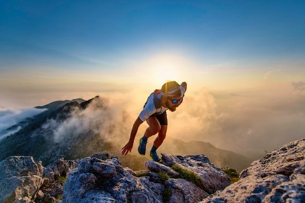 Uomo del corridore del cielo in salita sulle rocce al tramonto
