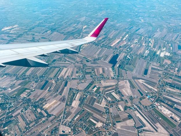 Finestra dell'aereo di vista del cielo nuvole e cieli luminosi durante il giorno formano sopra