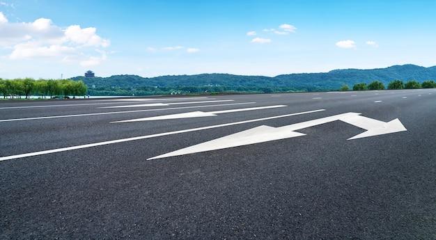 Orizzonte della pavimentazione dell'asfalto e del cielo blu e della nuvola bianca
