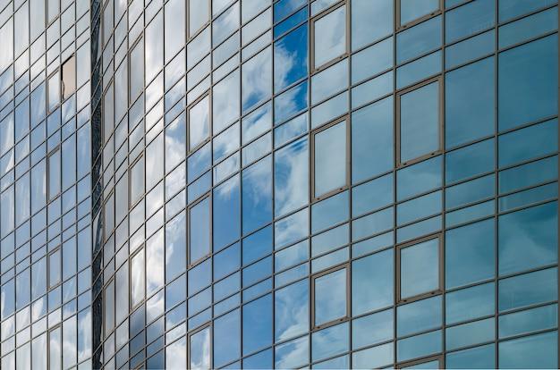 Superficie di vetro dello specchio del grattacielo che riflette cielo nuvoloso, superficie curvy