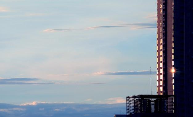Grattacielo con riflessi di luce solare contro il cielo nuvoloso