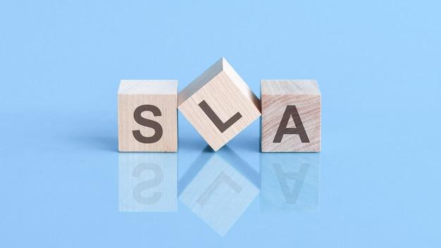 La parola sla è composta da cubi di legno sdraiati sul tavolo blu, concetto di business. sla abbreviazione di service level agreement