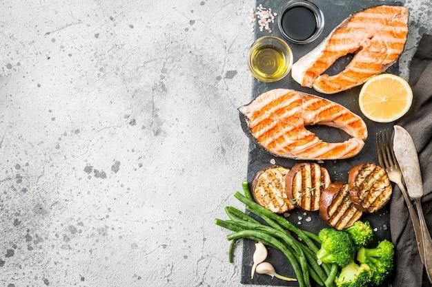 Piatto di ardesia con bistecche di salmone alla griglia e verdure su sfondo grigio, vista dall'alto