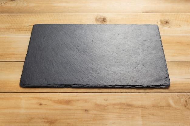 Cartello in pietra ardesia su tavola di legno, superficie della trama di sfondo