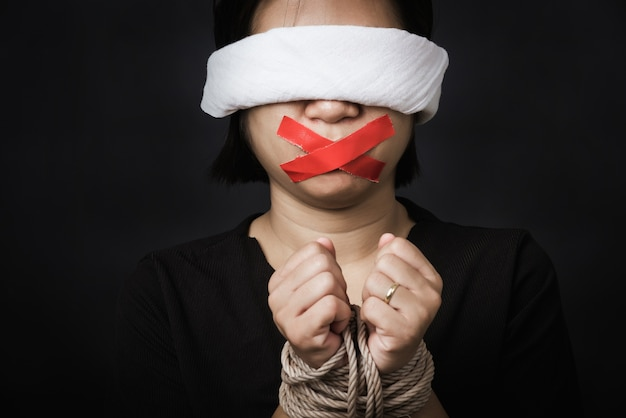 Schiava donna bendata che avvolge la bocca con nastro adesivo rosso, legata con catene e chiuse gli occhi