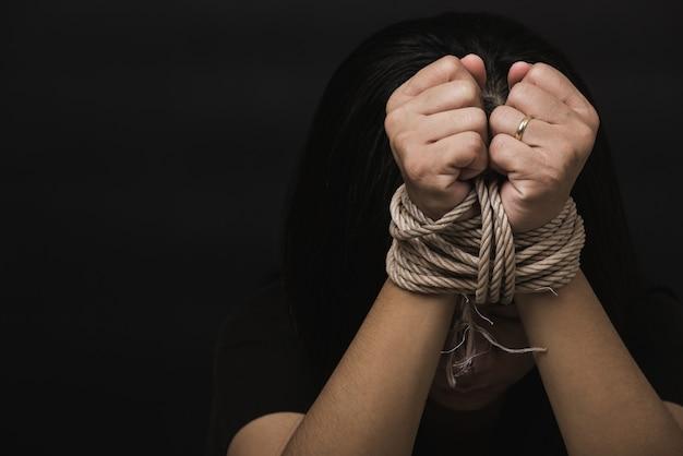 La donna schiava teme di essere legata alle mani con una corda