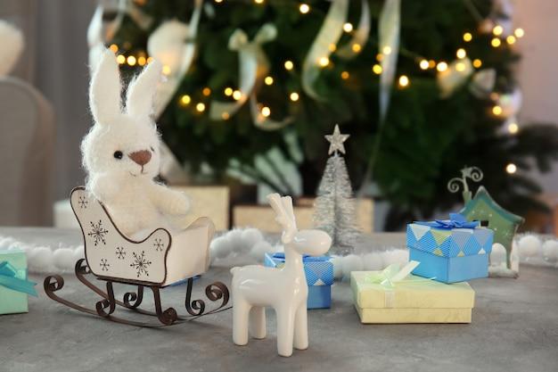Slitta con un simpatico giocattolo per bambini sul tavolo nella stanza decorata per natale