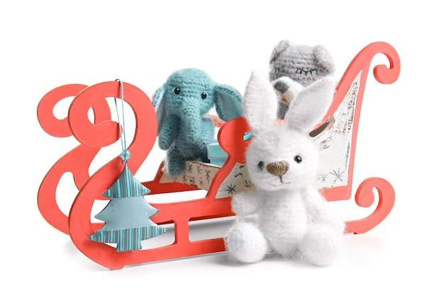Slitta con simpatici giocattoli sulla superficie della superficie bianca