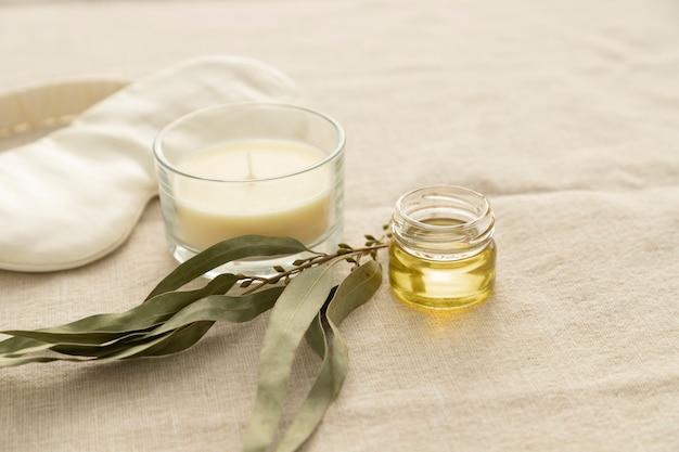 Trattamenti per la cura del sonno maschera per dormire in seta, branche di eucalipto essiccato, candela, olio essenziale di eucalipto, sfondo di lino