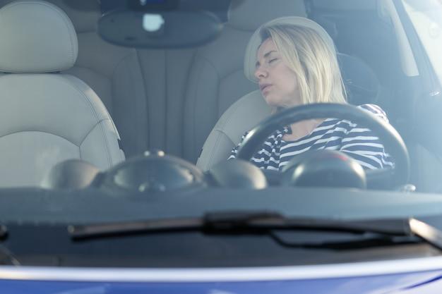 Dormire in macchina, l'autista stanca di guidare per una lunga strada ha un pisolino sul sedile anteriore al parcheggio