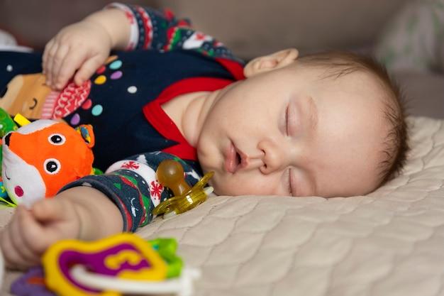 Bambino sveglio addormentato, tre mesi, con i giocattoli. messa a fuoco selettiva.