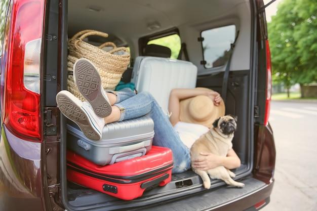 Ragazza addormentata nel bagagliaio di un'auto con carlino carino e bagagli. concetto di viaggio