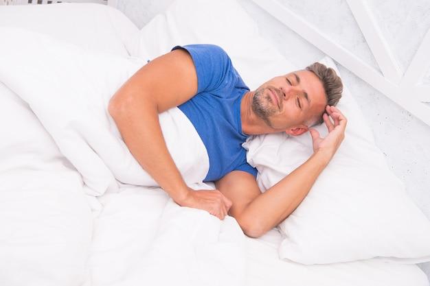 Bello addormentato. uomo barbuto che dorme faccia rilassante sul cuscino. bello e assonnato. uomo sexy che dorme a letto. il ragazzo sdraiato a letto cerca di rilassarsi e addormentarsi. godendo bella mattina.