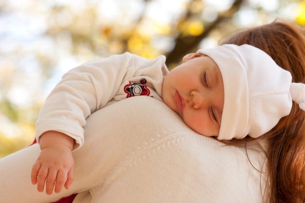 Bambina addormentata sulla spalla della madre nel parco autunnale