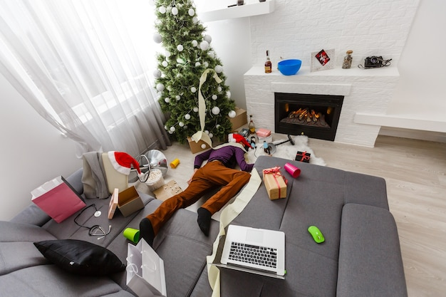 Uomo addormentato su un divano dopo la festa di natale.