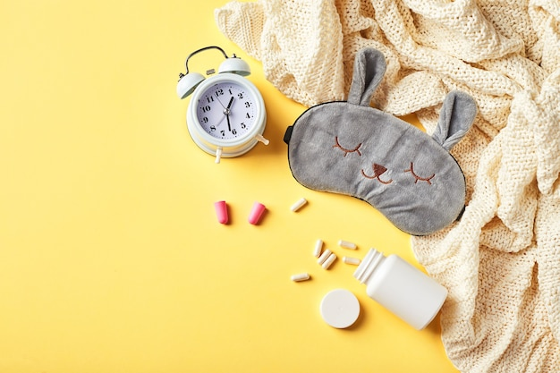 Maschera per dormire, sveglia, tappi per le orecchie e pillole. concetto creativo di sonno notturno sano. vista piana laico e dall'alto. buona notte, igiene del sonno, insonnia