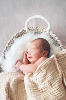Neonato addormentato nel cesto avvolto in una coperta in sfondo di pelliccia bianca