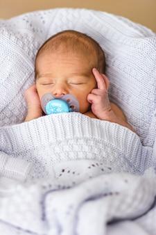 Neonato addormentato con un ciuccio. primo piano di babyface.