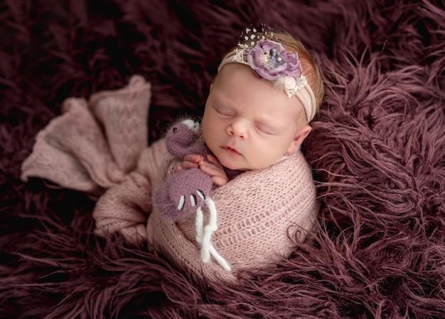 Neonato addormentato con orlo floreale che abbraccia un piccolo giocattolo
