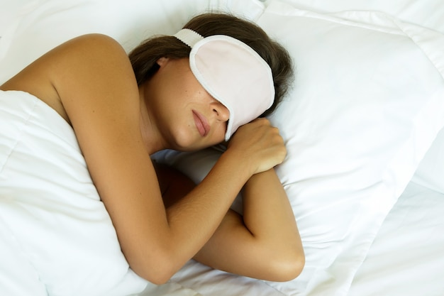 Donna addormentata con maschera per gli occhi