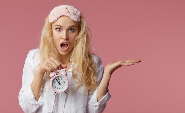 Giovane donna insonne in pigiama e maschere per dormire su una parete rosa. la sveglia ha svegliato la donna