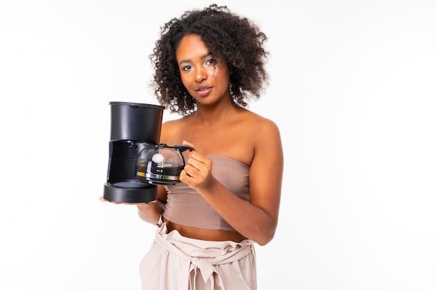La donna africana sonnolenta in estate copre con il creatore di caffè, immagine isolata su fondo bianco