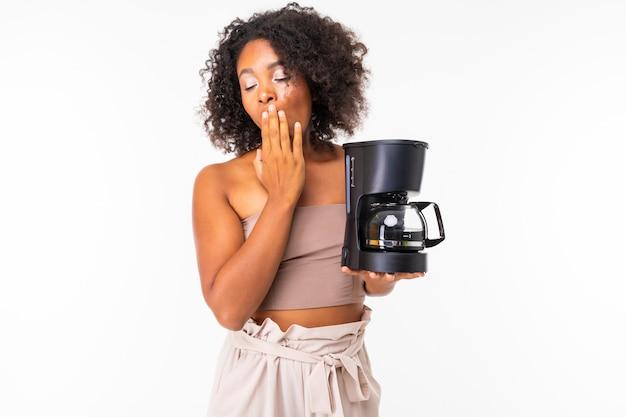 La donna africana sonnolenta in estate copre con la macchinetta del caffè, immagine isolata sulla parete bianca